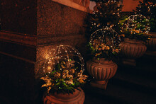 Christmas Decorations On The City Street, Christmas Trees And Gold Ornaments On The Steps Of The House
