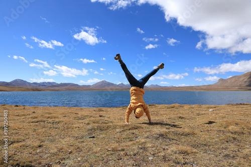 Fotografie, Tablou Woman doing handstand on high altitude grassland under blue sky