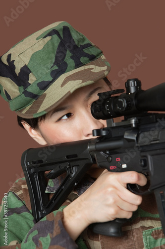 Fényképezés Young female Marine Corps soldier aiming M4 assault rifle over brown background