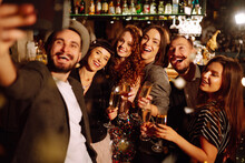 Selfie Time. Group Of Friends At A Nightclub Party Taking Selfie With The Phone. Young People Enjoying Having Drinks Together At The Bar And Make A Photo Of Themselves On A Phone. Winter Holidays.