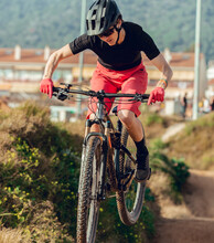 Sportswoman In Black Helmet And Red Sportswear With Glasses Riding Mountain Bike Jumping In Training Track