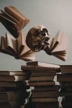 Opened Books And Scary Human Skull Levitating Over Heap Of Stacked Old Books