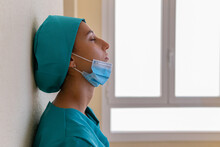Side View Of Tired Desperate Female Medic In Blue Uniform With Mask On Chin Leaning On Wall Of Hospital Corridor After Working Hard During Coronavirus Pandemic
