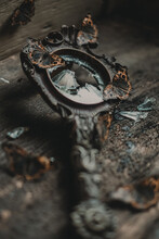 Butterflies Sitting On Antique Mirror With Carved Metal Frame And Broken Glass Shards On Weathered Wooden Table