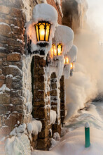 Exterior Of Aged Stone Building With Glowing Lanterns Covered With Snow And Steam Coming Out From Window In Wintertime