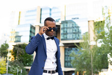 Low Angle Of Masculine African American Male Entrepreneur Wearing Elegant Suit And Sunglasses Standing In City And Looking Away