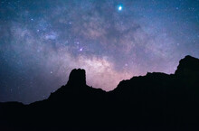 From Below Of Silhouette Of Rocky Hill On Background Of Breathtaking Night Sky With Milky Way In Tenerife