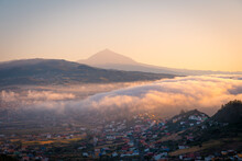 Spectacular Distant View Of City With Colorful Cottages Under Cloud Of Fog In Highland Valley In Morning In Tenerife