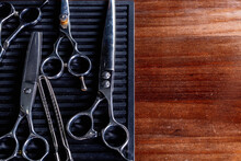 From Above Of Vintage Kit Of Various Hair Cut Scissors And Clamp Arranged On Black Board On Shabby Wooden Table