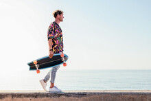 Low Angle Side View Of Young Hipster Male Skater In Trendy Summer Outfit Carrying Skateboard While Walking On Embankment Against Sea And Cloudless Sky In Summer Day