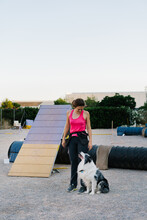 Full Length Of Female Owner And Border Collie Looking At Each Other While Preparing For Training On Dog Agility Equipment In Park