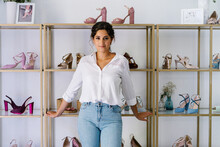 Charming Female In Casual Outfit Standing Near Wooden Shelves With Various High Heeled Shoes In Expensive Boutique And Looking At Camera