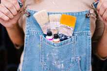 Crop Anonymous Female Artist In Denim Overall With Various Paintbrushes And Colorful Paint Tubes In Pocket