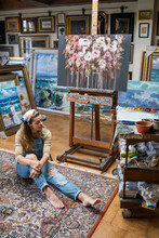 Female Artist In Denim Overall Sitting On The Floor Near Easel In Creative Atelier