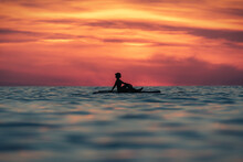 Silhouette Of Faceless Female Surfer Sitting On Paddle Board And Rowing Against Spectacular Sun In Sunset Sky