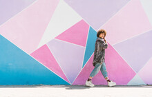 Smiling Woman Walking Against Multi Colored Wall