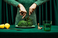 Midsection Of Woman Cutting Broccoli With Knife And Fork While Standing Against Green Curtain