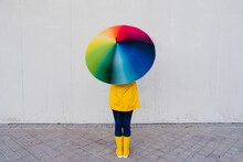Woman Holding Colorful Umbrella Standing In Front Of Gray Wall On Footpath