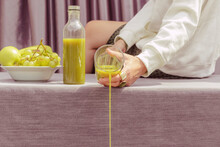 Close-up Of Woman Throwing Green Juice While Sitting On Table At Home