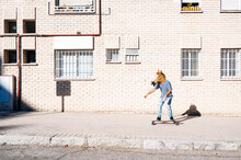 Man Wearing Horse Mask While Skateboarding On Footpath Against Building In City During Sunny Day