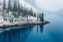Snowy Reflection Of Trees In Moraine Lake, Alberta, Canada