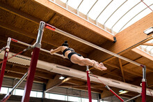 Young Artistic Gymnast Woman Performing And Training Uneven Bars