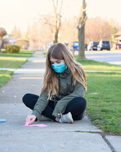 Child Drawing Heart Outside With Chalk With Mask