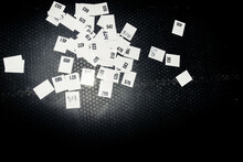 Sheets With Numbers Scattered On The Black Floor