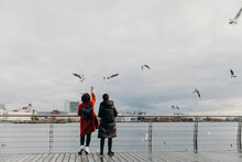 A Loving Couple Feeds Seagulls On The Bridge.