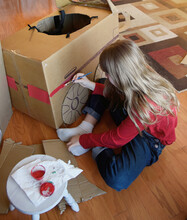 Creative Child Making Cardboard Car At Home With Paint.