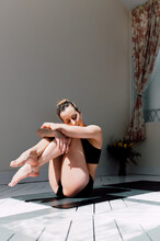 Tranquil Woman In Shoulder Stand With Legs In Lotus Pose