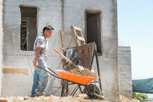 Hispanic Construction Worker Pushing Wheelbarrow At Construction Site