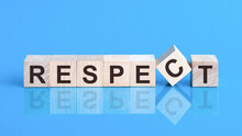 The Text Respect Is Written On The Cubes In Black Letters, The Cubes Are Located On A Blue Glass Surface