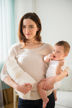 Mother Holding Baby And Stack Of Diapers