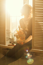 Caucasian Woman Holding Birdcage In Window