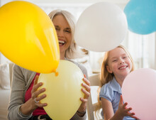 Senior Caucasian Woman And Granddaughter Playing With Balloons