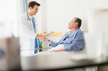 Caucasian Doctor Shaking Hands With Senior Patient In Hospital