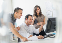 Hispanic Business People Cheering Together In Office