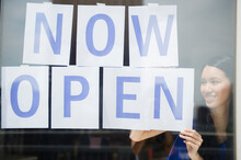 Woman Hanging Now Open Sign In Store Window