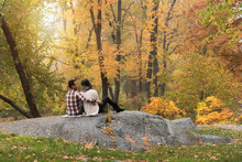 Asian Couple Hugging On Rock In Park