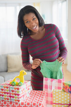 Black Pregnant Woman Admiring Gifts At Baby Shower