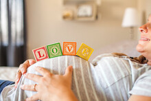 Pregnant Caucasian Woman Balancing Wooden Blocks On Her Stomach In Bed