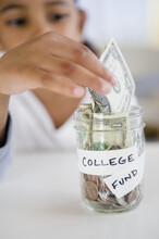 Mixed Race Girl Saving Money In College Fund Jar