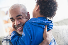 Close Up Of Mixed Race Grandfather And Grandson Hugging