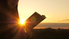 A Person Reads A Book In Sun. Man Reads Bible Outdoors. A Man Holds Bible In His Hands And Studies The Word Of God At Sunrise On Top Of Mountain. Searching For Truth In Scriptures.