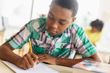 Black Student Writing In Classroom