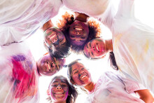 Low Angle View Of Smiling Friends Covered In Pigment Powder