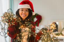 Pacific Islander Woman In Santa Hat Holding String Lights