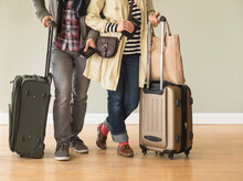 Couple Holding Rolling Luggage...