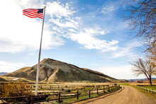 Low Angle View Of American Flag Over Dirt Road, Painted Hills, Oregon, United States